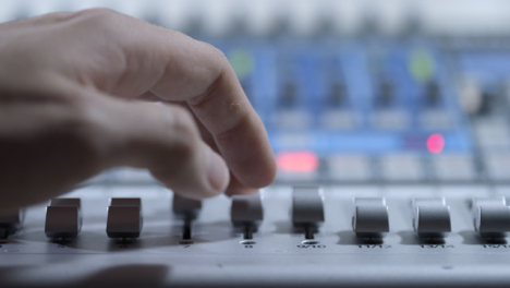 Tracking-Close-Up-Shot-of-Audio-Mixers-Hand-Adjusting-Faders-On-Audio-Mixing-Board