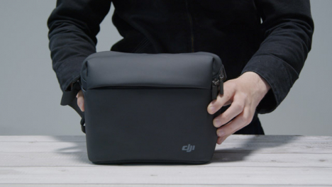 Tracking-Shot-Approaching-Person-Placing-DJI-Bag-On-Table