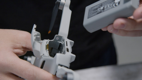 Close-Up-Shot-of-Person-Inserting-Battery-into-DJI-Mini-2