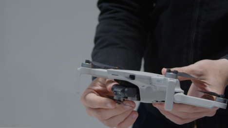 Close-Up-Shot-of-Person-Folding-Out-Arms-On-a-DJI-Mini-2
