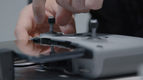 Close-Up-Shot-of-Person-Inserting-Joysticks-into-DJI-Drone-Controller