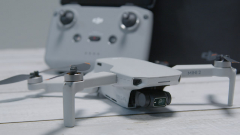 Tracking-Shot-Orbiting-DJI-Mini-2-Drone-and-Controller-On-Table-Surface