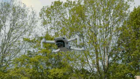 Low-Angle-Shot-Orbiting-DJI-Mini-2-Drone-Hovering-In-Air