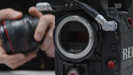 Close-Up-Shot-of-Person-Putting-Lens-On-RED-Dragon-Cinema-Camera