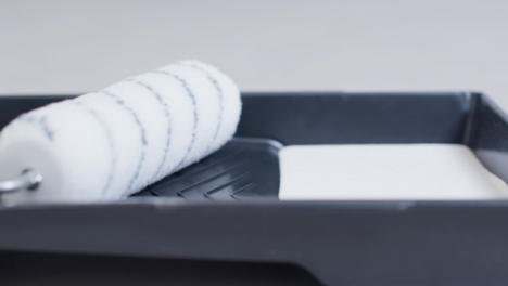 Sliding-Close-Up-Shot-of-White-Paint-In-Painting-Tray-with-Roller