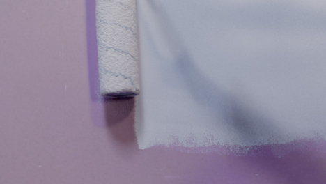 Close-Up-Shot-of-Paint-Roller-Applying-White-Paint-to-Pink-Wall-
