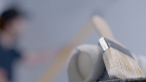 Close-Up-Shot-of-Paint-Brush-and-Roller-with-Person-Painting-In-Background