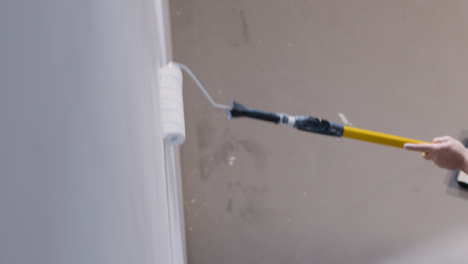 High-Angle-Shot-of-Paint-Roller-Applying-Paint-to-White-Wall