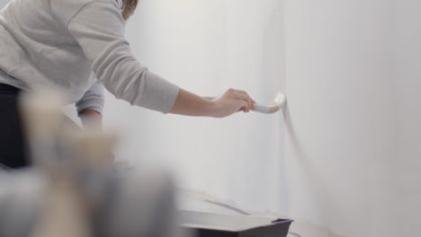 Pull-Focus-Shot-of-a-Person-Painting-White-Wall-with-Paint-Brush