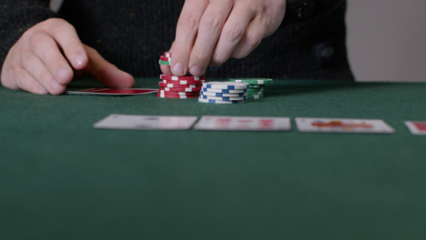 Sliding-Shot-of-Poker-Player-Checking-Cards-and-Placing-Bet
