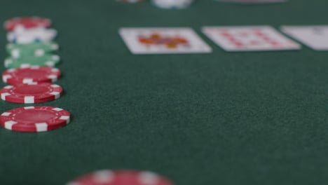 Tracking-Close-Up-Shot-from-Cards-to-Poker-Chips-Being-Thrown-In-