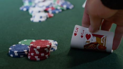 Tracking-Close-Up-Shot-of-Player-Checking-Their-Poker-Hand-Before-Going-All-In