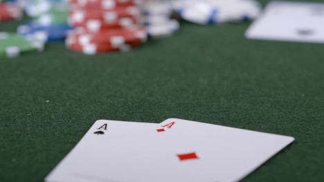 Extreme-Close-Up-Shot-of-Poker-Player-Going-All-In-and-Turning-Over-Pocket-Aces