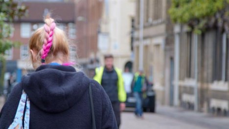 Tracking-Shot-Following-Person-with-Pink-Hair-In-Street