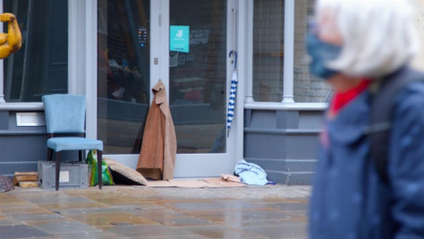 Long-Shot-of-Homeless-Persons-Belongings-In-Disused-Shop-Entrance