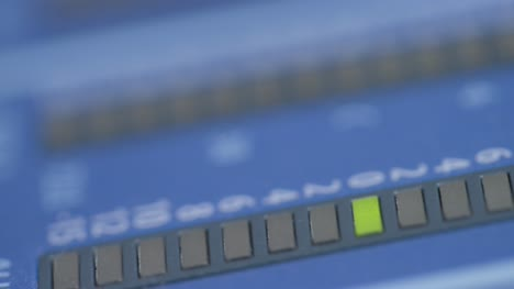 Tracking-Extreme-Close-Up-Shot-of-Gain-Lights-On-Sound-Mixing-Board