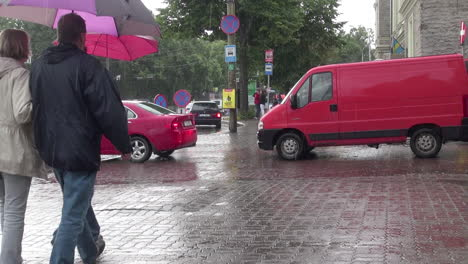 Tallinn-Estonia-red-van-and-car-and-people-with-umbrellas
