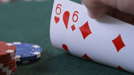 Extreme-Close-Up-Shot-of-Poker-Player-Checking-Their-Cards-