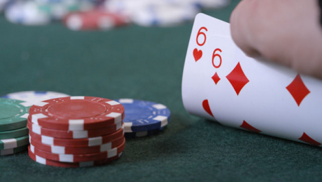 Extreme-Close-Up-Shot-of-Poker-Player-Looking-at-Their-Cards-Before-Checking