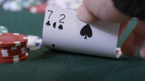 Extreme-Close-Up-Shot-of-Poker-Player-Looking-at-Seven-Deuce-Before-Folding