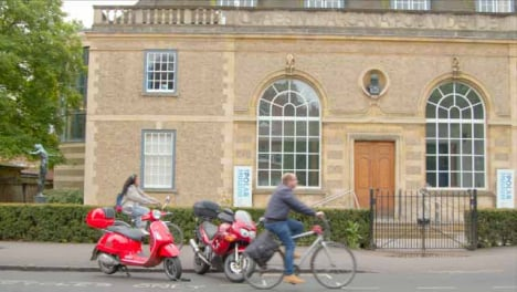 Tracking-Shot-of-Cyclists-Passing-In-Front-of-Scott-Polar-Research-Institute-Museum
