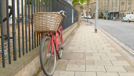 Tracking-Shot-Orbiting-Red-Bicycle-Tied-to-Railing