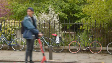 Wide-Shot-of-Person-On-Electric-Scooter-Passing-In-Front-of-Bicycles