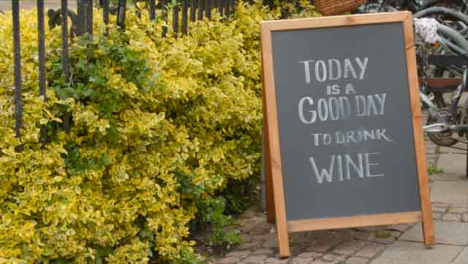 Tracking-Shot-Orbiting-Blackboard-Sign-Reading-Today-Is-a-Good-Day-to-Drink-Wine