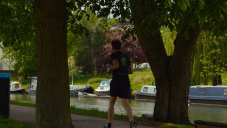Tracking-Shot-of-Runner-On-Footpath-Next-to-River-Cam