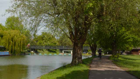 Tracking-Shot-of-Cyclist-Riding-Along-Path-Next-to-River-Cam