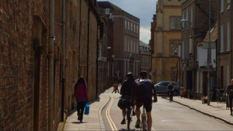 Tracking-Shot-of-Cyclists-Riding-Down-Quiet-Old-English-Backstreet
