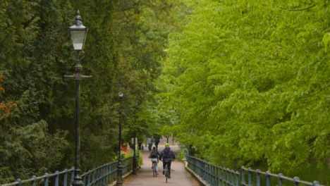 Tracking-Wide-Shot-of-Cyclists-Riding-Down-Path-Under-Trees