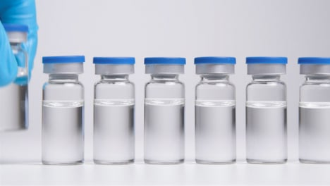 Tracking-Shot-Pulling-Away-from-Line-of-Vials-of-Translucent-Liquid-Before-Hand-Takes-One-Away