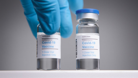 Low-Angle-Tracking-Shot-Approaching-Covid-19-Vaccine-Vials-Before-Hand-Takes-One-Away-