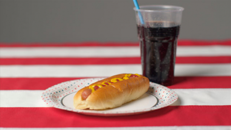 Sliding-Shot-of-Hot-Dog-and-Soda-On-Striped-Table-Cloth