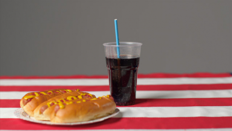Sliding-Shot-of-Hot-Dogs-and-Soda-On-Striped-Table-Cloth