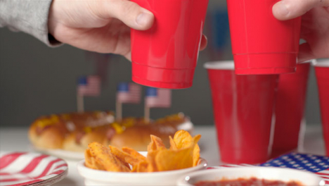 Sliding-Shot-Over-Party-Food-as-People-Bring-Cups-Together-In-a-Cheers