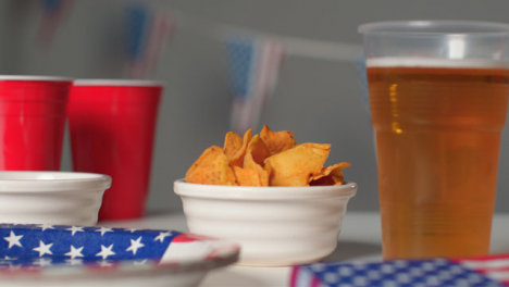 Sliding-Shot-Approaching-Plastic-Cup-of-Beer-and-Small-Bowl-of-Nachos