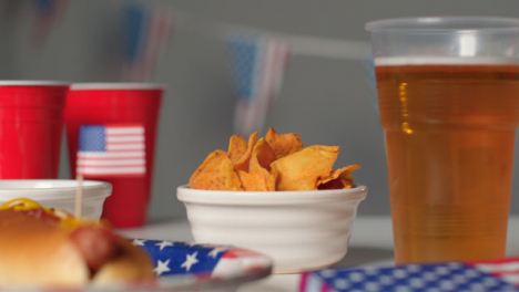 Sliding-Shot-Approaching-Plastic-Cup-of-Beer-and-Bowl-of-Nachos
