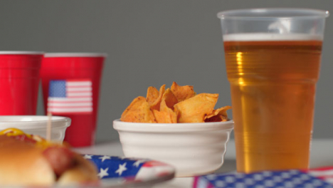 Sliding-Shot-Approaching-Plastic-Cup-of-Beer-and-a-Bowl-of-Nachos