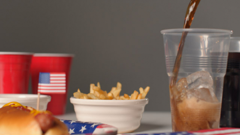 Sliding-Shot-Approaching-Bowl-of-Fries-and-Cola-Being-Poured