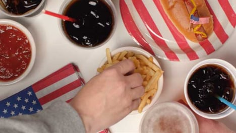 Top-Down-Shot-of-Hands-Taking-Fries-and-Beer-from-Party-Food-Spread