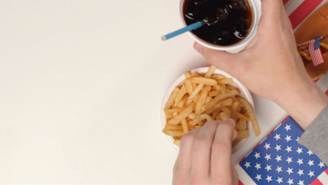Top-Down-Shot-of-Hands-Taking-Fries-and-Soda-from-Table-with-Copy-Space