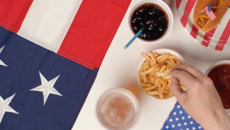 Top-Down-Shot-of-Hands-Taking-Fries-and-Beer-from-July-4th-Party-Food-Spread