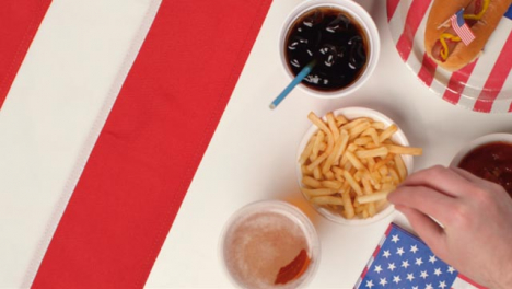 Top-Down-Shot-of-Hands-Taking-Fries-and-a-Beer-from-July-4th-Party-Food-Spread
