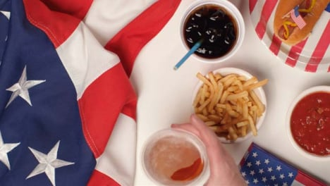 Top-Down-Shot-of-Hands-Taking-Fries-and-a-Beer-from-a-July-4th-Party-Food-Spread