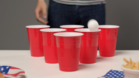 Sliding-Shot-Approaching-Cups-as-Person-In-Background-Drinks-During-Beer-Pong-Game