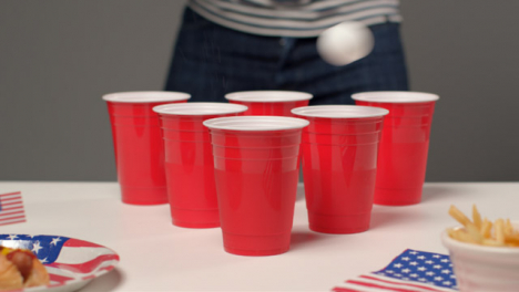 Sliding-Shot-Approaching-Plastic-Cups-as-a-Person-In-the-Background-Plays-Beer-Pong