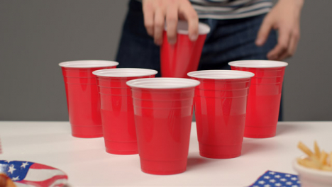 Sliding-Shot-Approaching-Cups-as-Person-In-Background-Drinks-During-a-Beer-Pong-Game