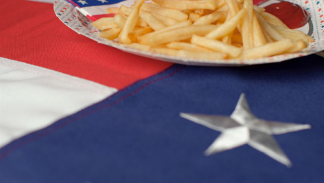 Extreme-Close-Up-Shot-of-Rotating-United-States-Flag-with-Bowl-of-Fries-and-Cup